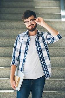 Occhiali d'uso dello studente allegro che posano con i libri di testo dopo le lezioni