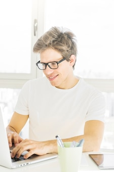 Occhiali d'uso sorridenti dell'uomo che per mezzo del computer portatile a casa