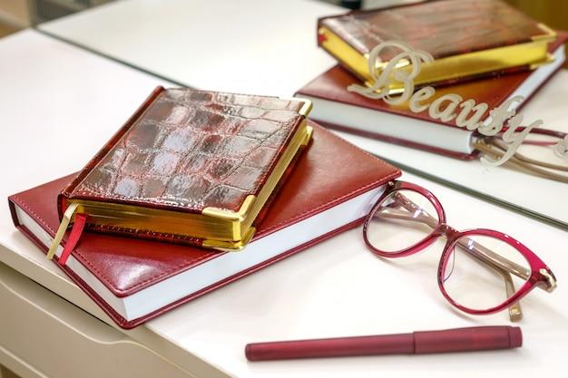Occhiali da notepad e una penna sono sul tavolo di fronte a uno specchio