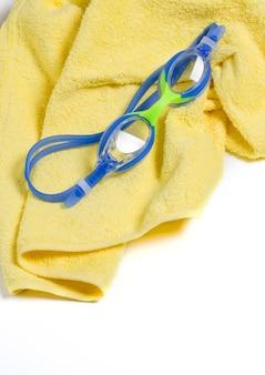 Occhiali da nuoto blu su un asciugamano giallo.