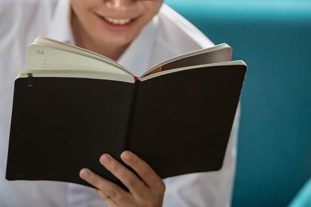 Occhiali da portare del giovane che leggono un libro sullo strato.