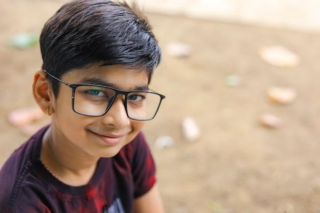 Occhiali da portare del piccolo ragazzo indiano / asiatico sveglio