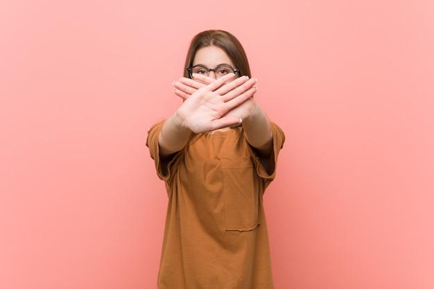 Occhiali da portare della giovane donna dello studente che fanno un gesto di rifiuto