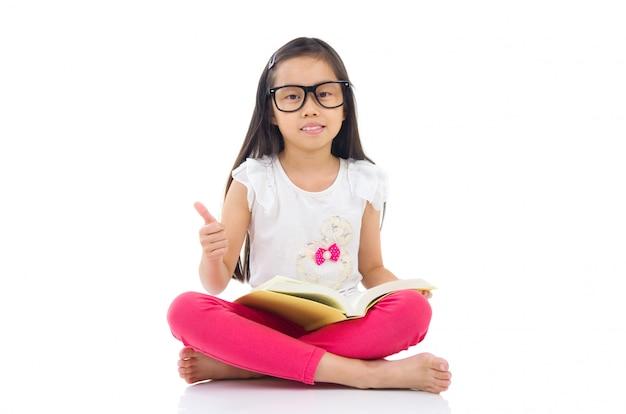 Occhiali da portare della ragazza asiatica che si siedono sul pavimento con i libri