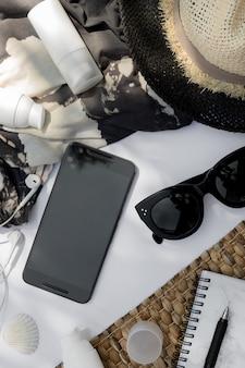 Occhiali da sole alla moda, planner, cappello e crema cosmetica con ombra di foglia di palma su sfondo bianco