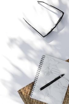 Occhiali da sole alla moda, planner con ombra foglia di palma su sfondo bianco
