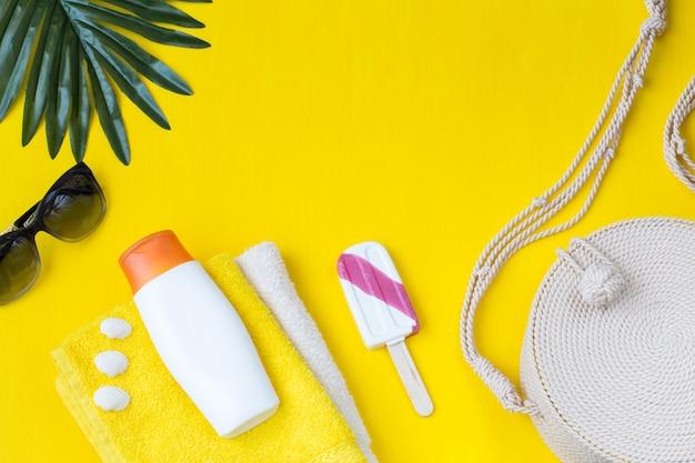 Occhiali da sole, asciugamani, foglia di palma, crema solare, borsa, conchiglie e gelato