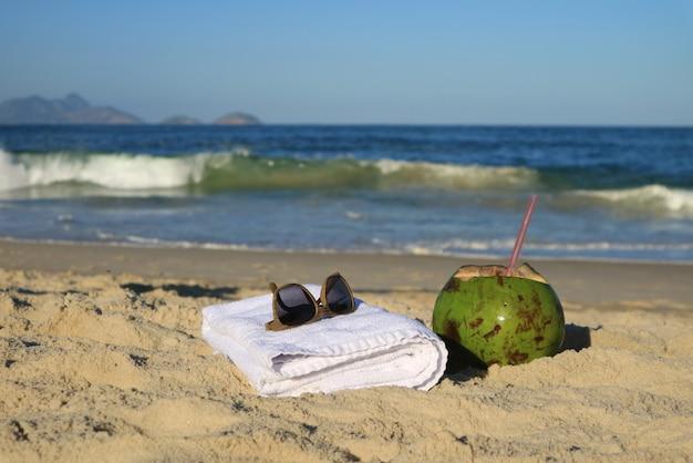 Occhiali da sole, asciugamano e una noce di cocco fresca giovane sulla spiaggia sabbiosa, copacabana, rio de janeiro, brasile