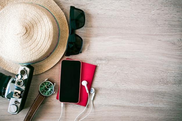Occhiali da sole, cellulari con fotocamera, cuffie, passaporti metti sul pavimento di legno per preparare il weekend.