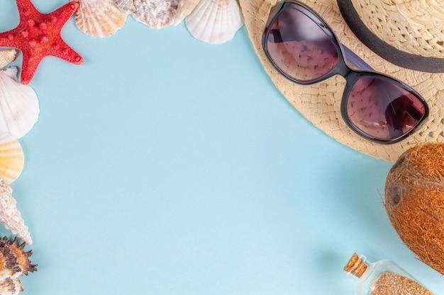 Occhiali da sole, cocco, stelle marine, conchiglie, cappello di paglia e bottiglia con sabbia su sfondo blu