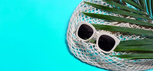 Occhiali da sole con borsa a rete sul blu. goditi il concetto di vacanza.