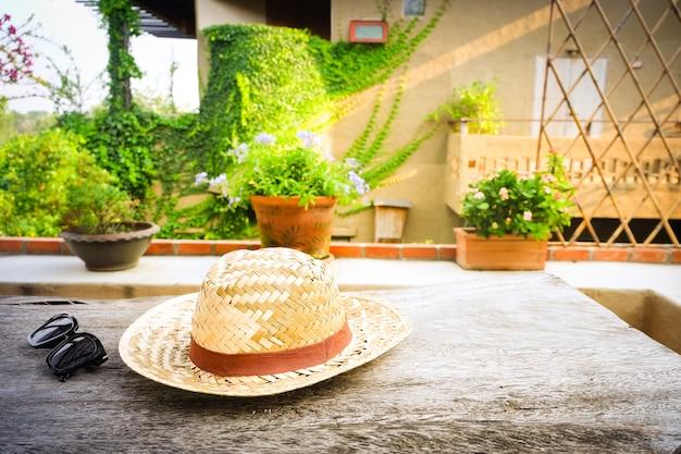 Occhiali da sole con cappello di paglia vintage fasion sul tavolo di legno