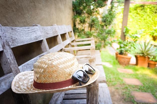 Occhiali da sole con cappello di paglia vintage fasion sulla sedia, sfondo per hotel resort d'epoca