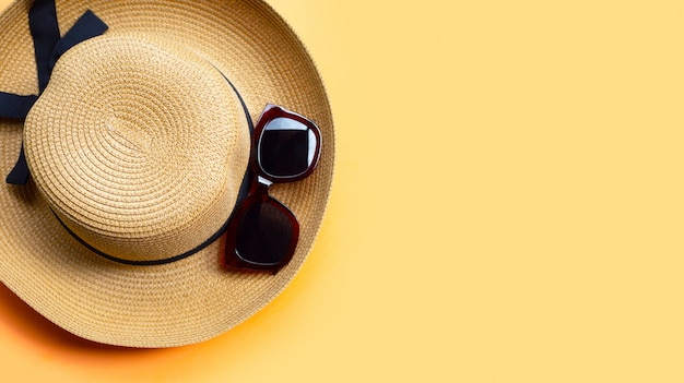 Occhiali da sole con cappello estivo su sfondo arancione. goditi il concetto di vacanza.