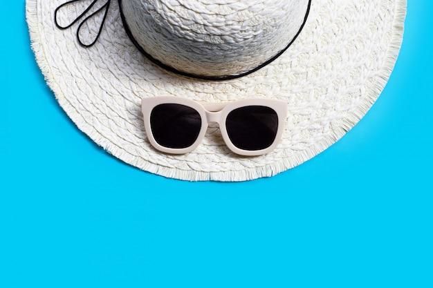 Occhiali da sole con cappello estivo su sfondo blu. goditi il concetto di vacanza.