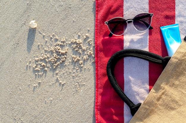Occhiali da sole con crema solare e borsa sul telo rosso.