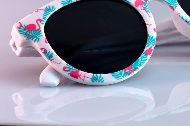 Occhiali da sole, con icone di fenicotteri, rosa, su uno sfondo bianco con riflessi