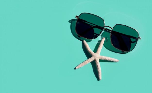 Occhiali da sole con pesci stella su sfondo blu. goditi il concetto di vacanza.
