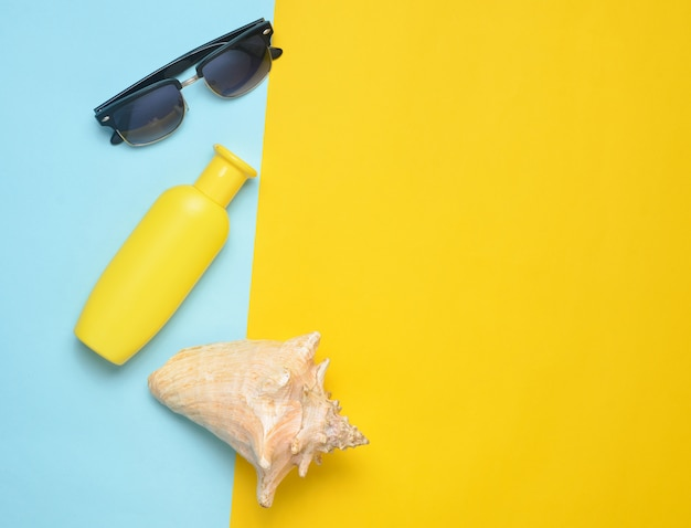 Occhiali da sole, crema solare, shell su uno sfondo giallo blu. stazione balneare estiva. vista dall'alto.
