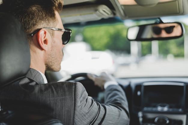 Occhiali da sole d'uso dell'uomo bello che esaminano specchietto retrovisore in automobile