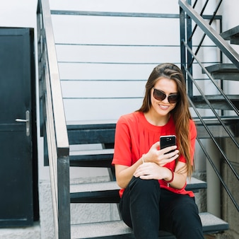 Occhiali da sole d'uso della donna alla moda che si siedono sullo stiarcase facendo uso del cellulare