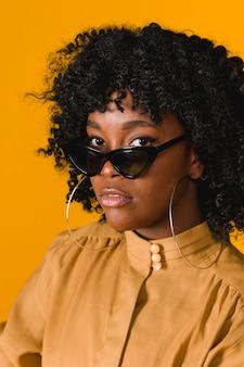 Occhiali da sole d'uso della giovane donna di colore che esaminano macchina fotografica
