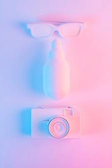 Occhiali da sole dipinti; lampadina led e macchina fotografica d'epoca su sfondo rosa