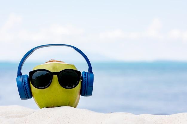 Occhiali da sole e auricolari d'uso della noce di cocco per rilassarsi e ascoltare musica sulla spiaggia contro il bei mare, vacanza e festa nel concetto di estate