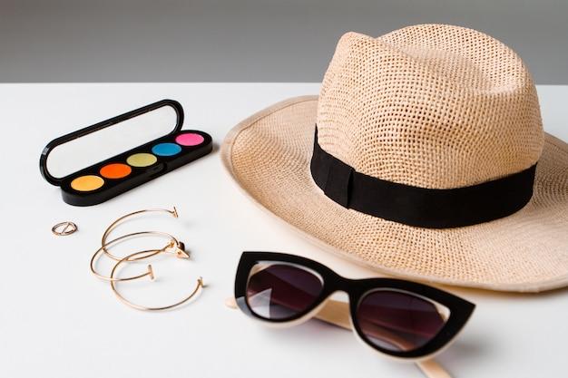 Occhiali da sole e cappello decorativi degli accessori dei cosmetici sulla tavola bianca.