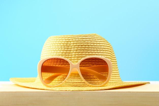 Occhiali da sole e cappello gialli su uno scaffale di legno su un fondo pastello blu. minimalismo.