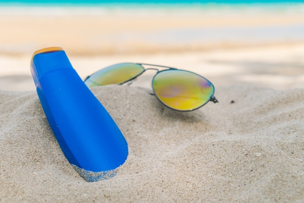 Occhiali da sole e crema solare sulla spiaggia di sabbia bianca