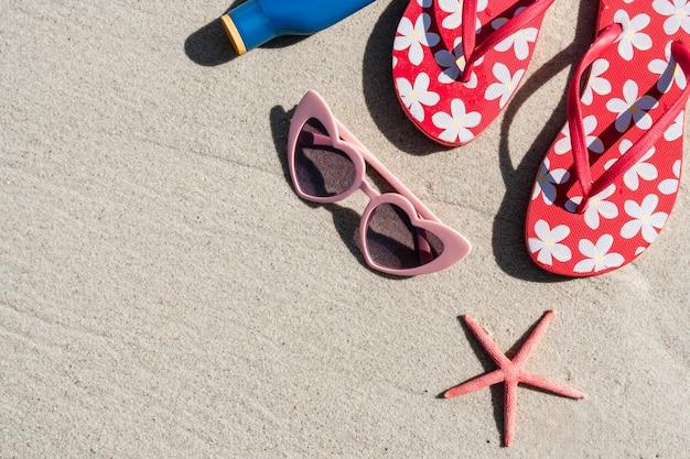 Occhiali da sole e infradito sulla spiaggia tropicale di sabbia bianca, vacanze estive e concetto di viaggio