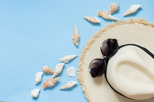 Occhiali da sole e occhiali da sole in paglia sulla spiaggia blu intenso.
