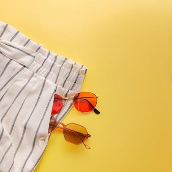 Occhiali da sole e pantaloncini vista superiore sfondo giallo brillante piatto singolo.