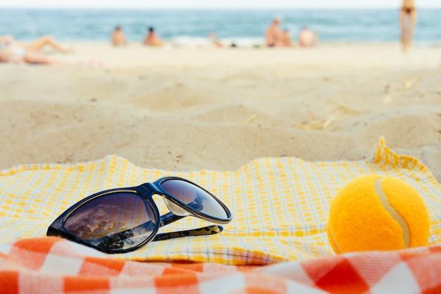 Occhiali da sole e una pallina da tennis che si trova su una coperta sullo sfondo della spiaggia in estate