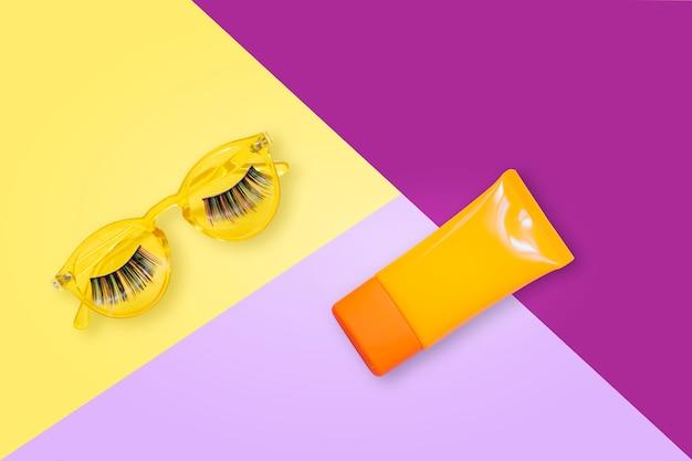 Occhiali da sole gialli con ciglia finte e crema solare spf crema solare su sfondo viola.