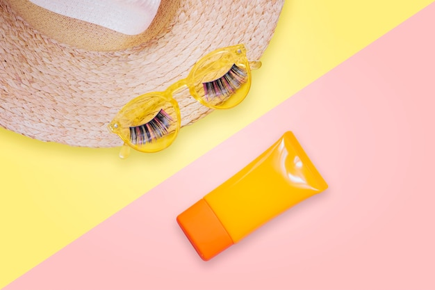Occhiali da sole gialli con ciglia finte su cappello di paglia e crema solare spf crema su sfondo rosa.