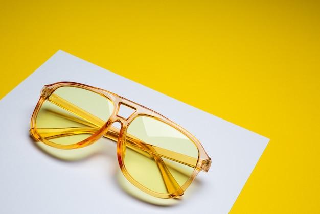 Occhiali da sole gialli femminili alla moda isolati su fondo astratto di carta bianco e giallo con spazio per testo