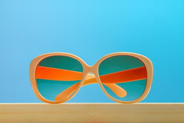 Occhiali da sole gialli su una mensola di legno su una priorità bassa pastello blu. minimalismo.