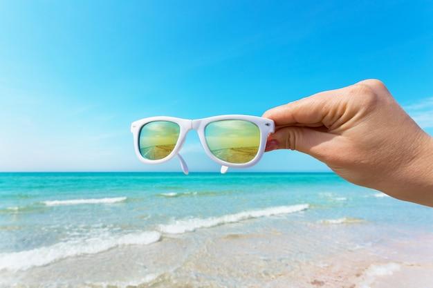 Occhiali da sole in mano sulla spiaggia