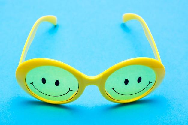 Occhiali da sole in plastica gialla con occhi dipinti e un sorriso sul vetro