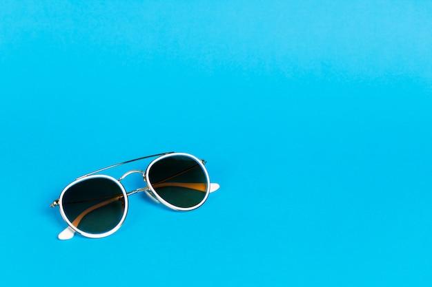 Occhiali da sole in una cornice bianca isolata su un blu.