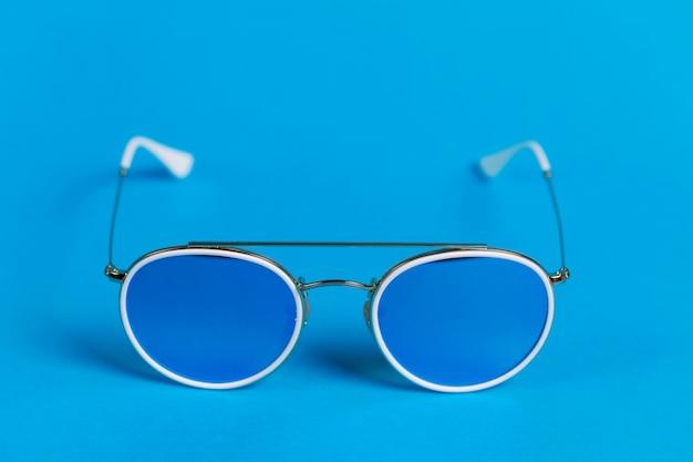 Occhiali da sole in una cornice bianca isolata su uno sfondo blu