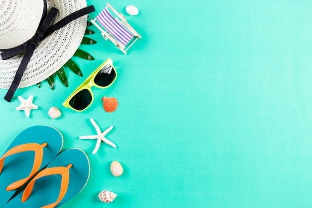Occhiali da sole, infradito stelle marine, cappello sulla parete verde pastello per vacanze estive e vacanze.