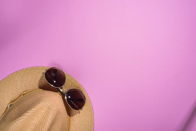 Occhiali da sole marroni e cappello a strisce retrò su sfondo viola con spazio di copia