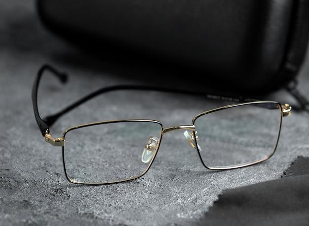 Occhiali da sole moderni di vista frontale moderni sullo sfondo grigio hanno isolato l'eleganza degli occhiali di visione