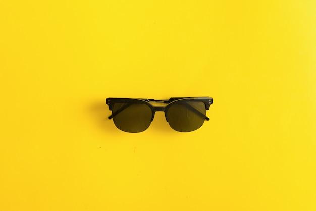 Occhiali da sole neri su sfondo giallo, estate concetto di protezione uv