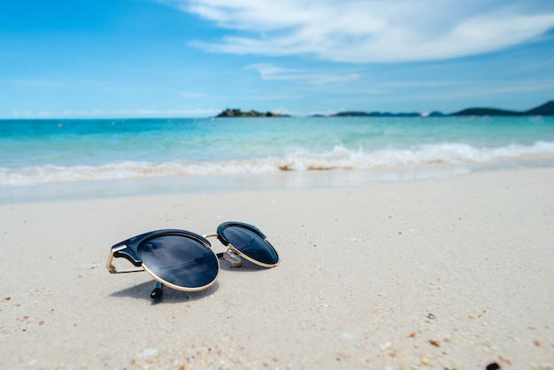 Occhiali da sole neri sullo sfondo del mare. bellissima spiaggia di sabbia come estate, viaggi e vacanze concetto. concetto di vacanza. agghiacciante sul mare. copia spazio per messaggio.