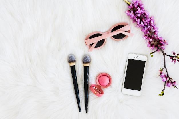 Occhiali da sole rosa; ramoscello di fiori viola; cipria compatta; pennelli trucco e telefono cellulare sullo sfondo di pelliccia
