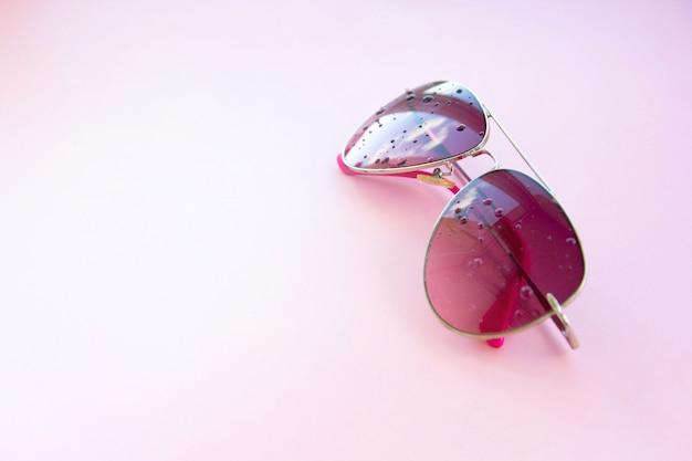 Occhiali da sole rosa su uno sfondo rosa, con riflessi, minimalista, copia spazio.